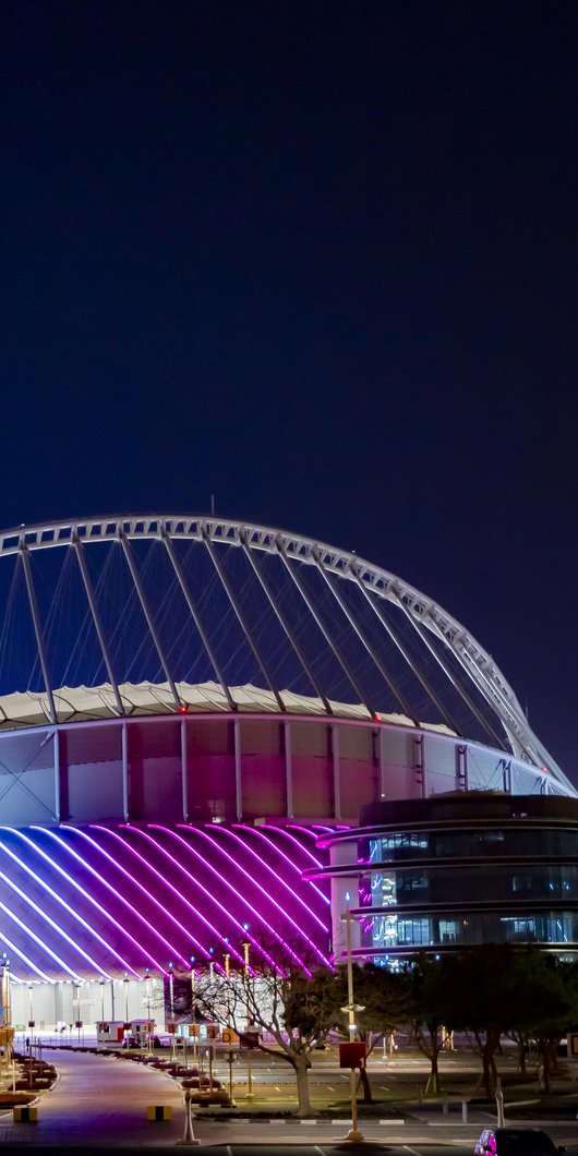 متحف قطر الأولمبي الرياضي مضاء ليلاً بألوان ضوئية ساطعة