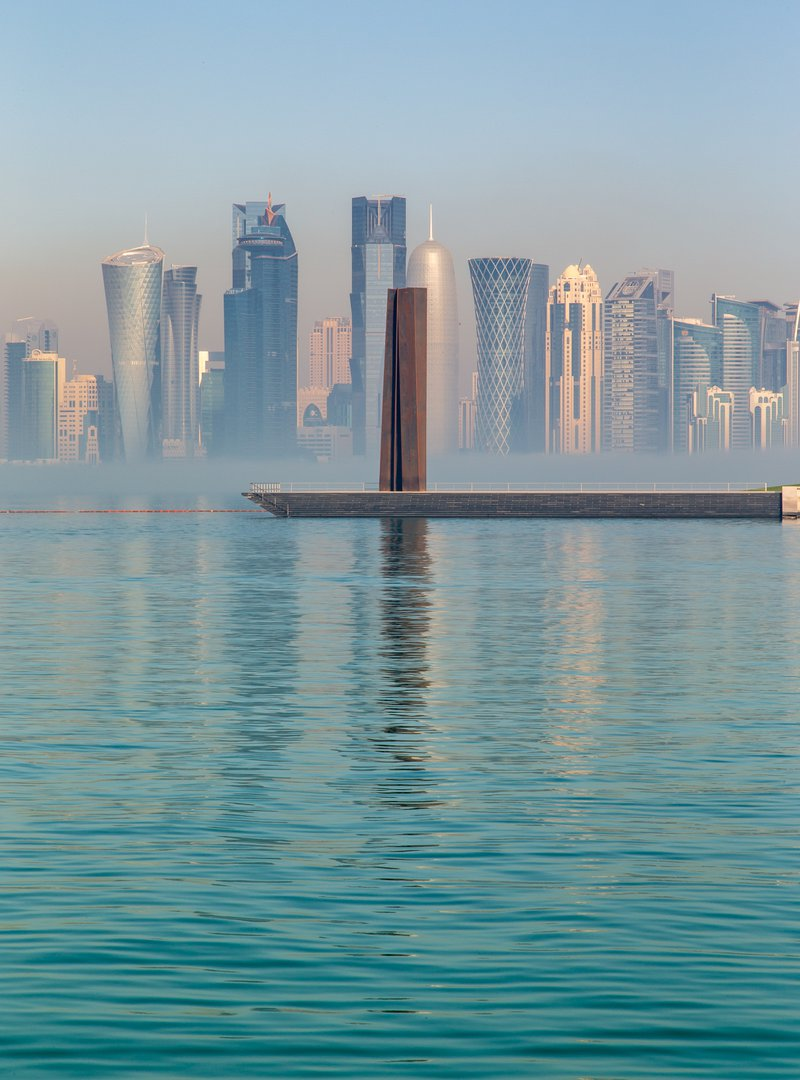 A portrait shot of Richard Serra's sculpture '7' located at MIA against Doha's iconic skyline