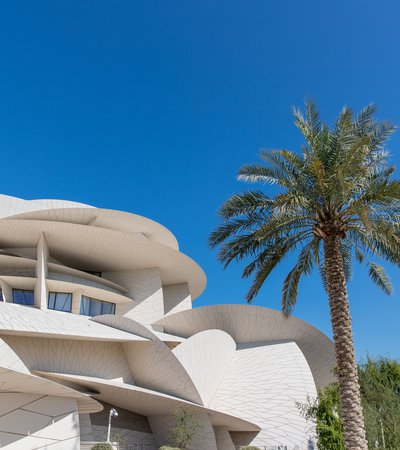 An exterior shot of the National Museum of Qatar and one of the surrounding palm trees