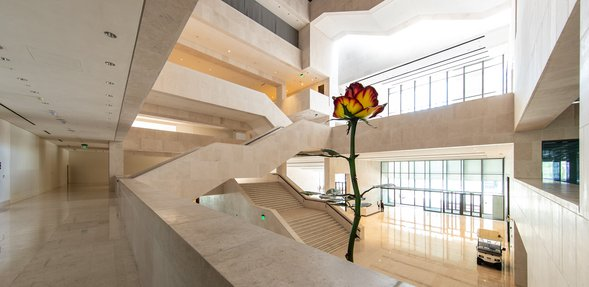 A two-story tall metal sculpture of a rose with red and white petals inside the entrance to the M7 building.