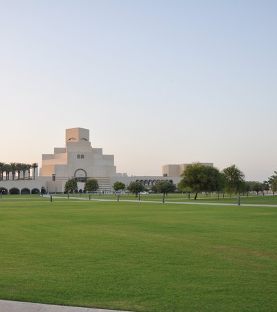 Wide angle of MIA Park, with green grass, blue sky and the museum in the background