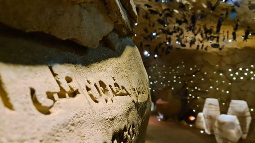 Interior of Cave of Wonders at National Museum of Qatar. There are Arabic letters carved on the cave walls with sunlight filtering through.