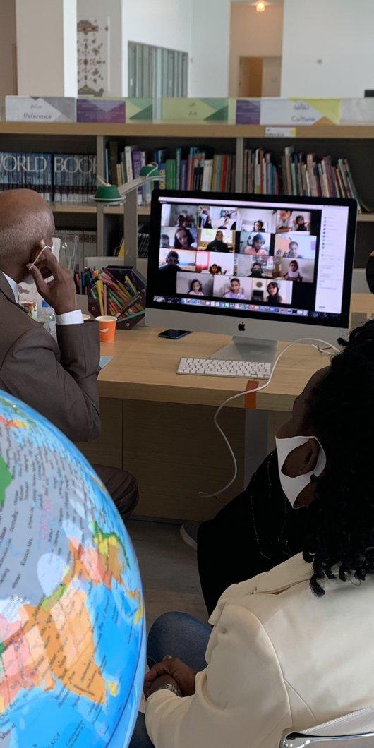 رجل وامرأة يجلسان أمام جهاز كمبيوتر داخل متحف الفن الإسلامي ويستضيفان فعالية كوكب الأطفال عبر برنامج زووم