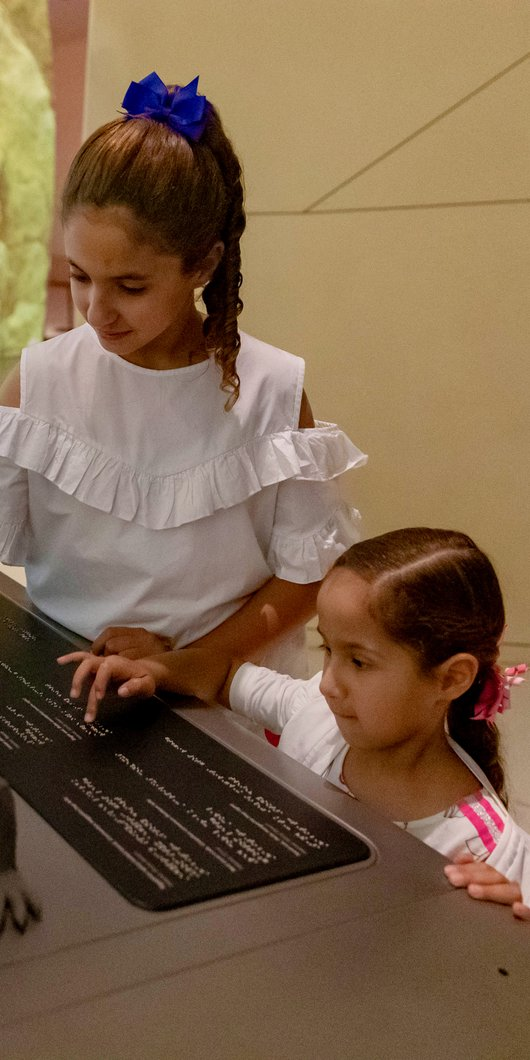 Two children use tactile accessible information panels at NMoQ