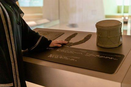 Woman using tactile accessible information panels at NMoQ