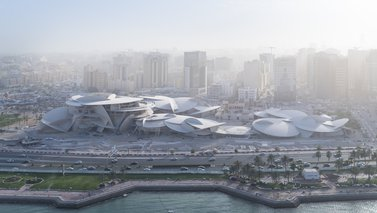 Aerial view showing the National Museum of Qatar with the sea in front and tall buildings behind it
