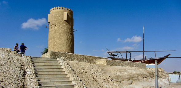The Al Khor stone tower with two people standing at the top of a flight of steps leading to the tower