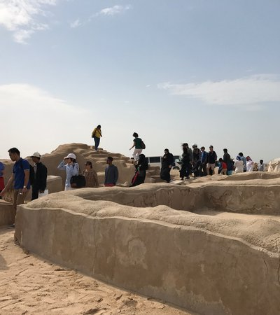 A queue of visitors walking through the clay structures of the heritage site