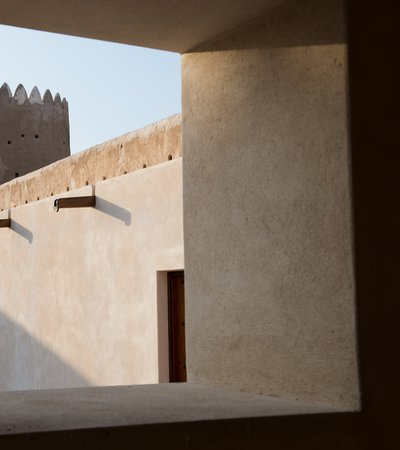 A close-up view from inside the Al Zubarah Fort showing its clay walls, wooden shafts and doors