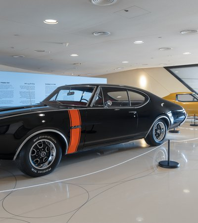 Two vintage American cars, one black and one yellow, parked in the Mawater Gallery, NMoQ