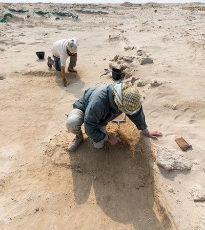 Two men kneeling on sandy desert ground using small tools to expose archeological remains at Al Zurbarah, Qatar