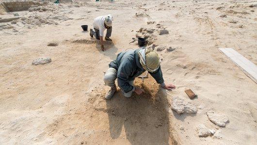 رجلان يستخدمان أدوات صغيرة للكشف عن البقايا الأثرية في موقع الزبارة الأثري في قطر.