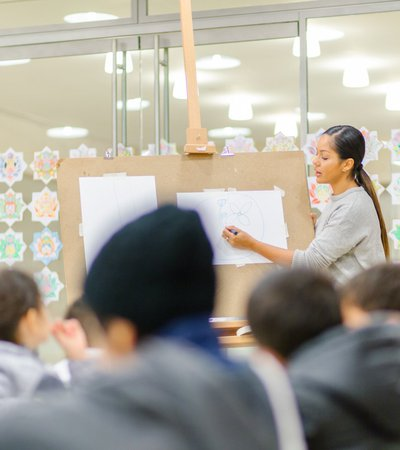 Teacher showing the children how to draw a flower on a board