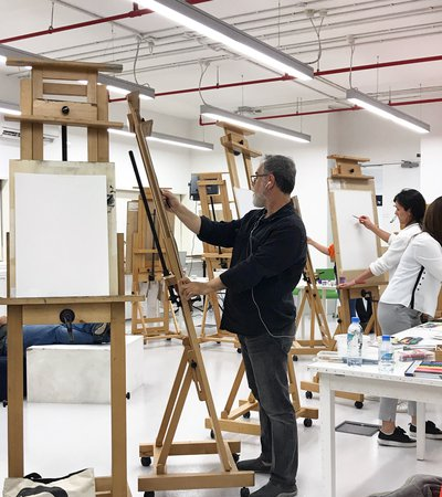 A room with multiple easels where a man stands drawing on one of them