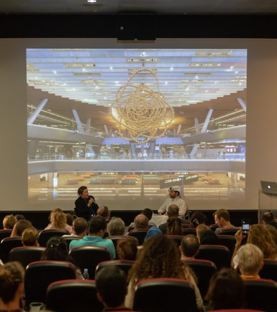 A wide shot of an auditorium showing Jean-Michel Othoniel talking about his work Cosmos to the audience