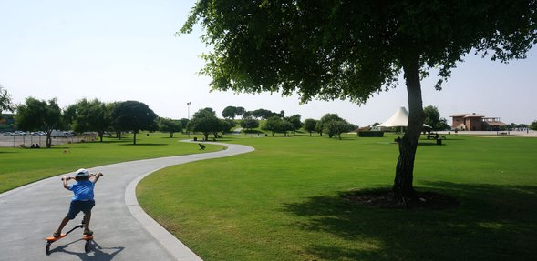 Aspire Park with a child riding his scooter on a pathway surrounded by green patches and trees