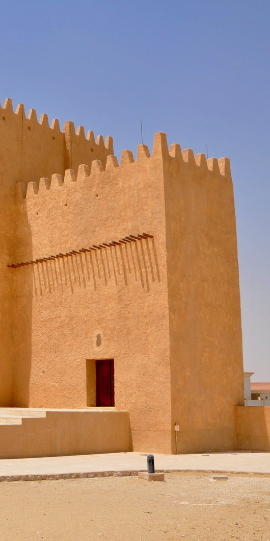 برج طويل الزوايا مصنوع من مادة من لون الرمل مع مدخل مفتوح وأسوار حول الجزء العلوي من المبنى.
