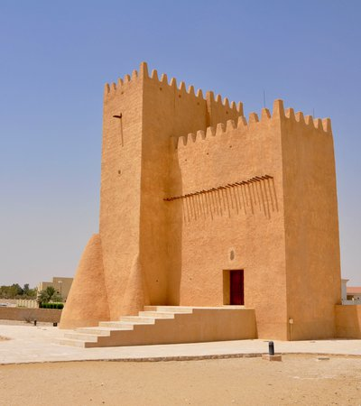A tall angular tower made from sand coloured material with an open doorway and crenellations around the top of the building