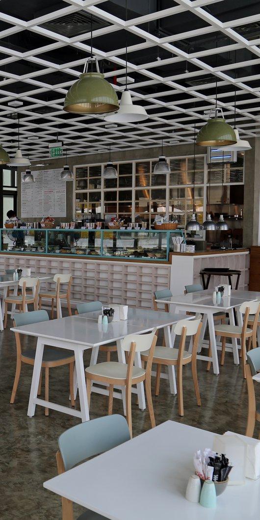 لقطة تُبرز التصميم الداخلي المعاصر لمقهى #999 وتُظهر مجموعة من الطاولات والكراسي إضافة إلى طاولة الخدمة