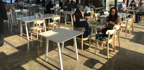 لقطة تُبرز التصميم الداخلي لمقهى #999 المكتظ بالزبائن الذين يتمتعون بتناول الأطعمة والمشروبات المتنوعة