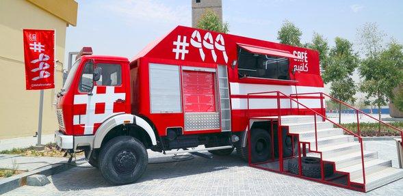 سيارة إطفاء حمراء اللون وشاحنة لبيع الأطعمة خارج مقهى #999 مع أدراج مؤدية إلى شباك تقديم الأطعمة ويظهر برج شاهق في الخلفية