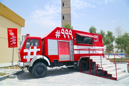 Cafe #999's red fire engine and food truck parked outside with steps leading up to the serving hatch and a tall tower in the background