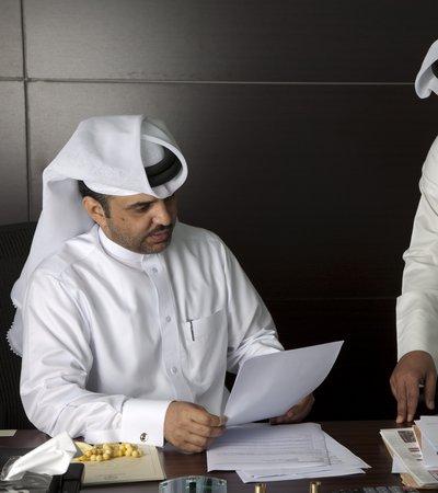 Two men in traditional Qatari attire study a document