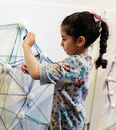 A young child making geometric shapes on a wall with string, at Dadu, Children's Museum
