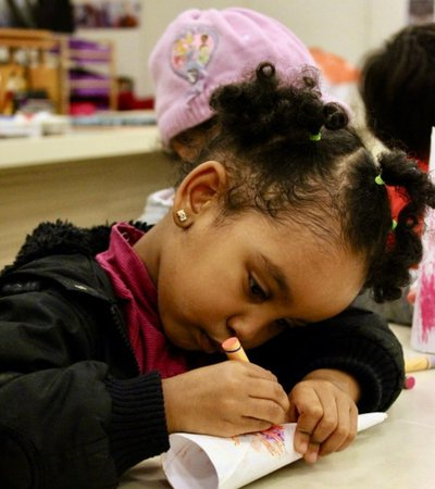 A small child focuses whilst they draw