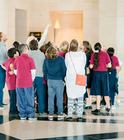 A photograph of a group of children standing in the lobby of MIA looking skywards