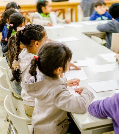 Children listening to their teacher talk in a classroom