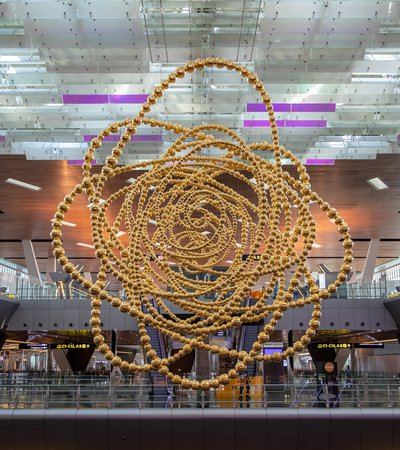 A large golden sculpture 'Cosmos' constructed of many concentric circular shapes suspended from the ceiling within an airport terminal