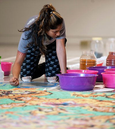 A young artist sits on the floor while working on an art piece made of powder colour