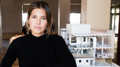 Portrait of Dasha Zhukova leaning against a table featuring an architectural model