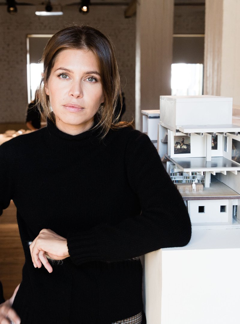 صورة داشا جوكوفا متكئة على طاولة عليها نموذج معماري