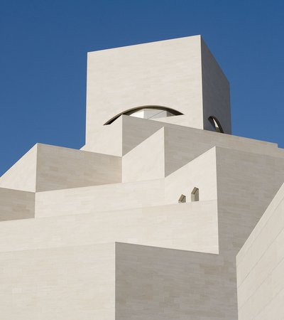 Detail of the white angular exterior of the Museum of Islamic Art with a blue cloudless sky in background