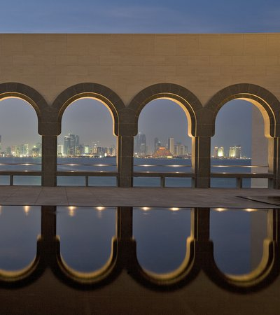 Nighttime view of Doha from the Museum of Islamic Art looking through a wall of arches
