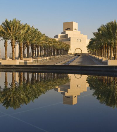 The main approach to the Museum of Islamic Art with palm trees on either side and its facade reflected in water