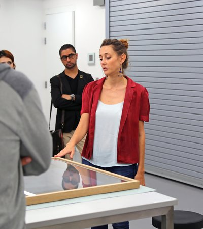A woman showing a glass framed art object to a group of teachers