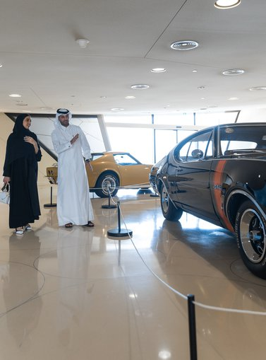 A man in Thobe and a woman in Abaya looking at the American muscle cars exhibited at NMoQ