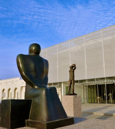 Exterior view of Mathaf: Arab Museum of Modern Art building with a group of three large sculptures positioned in front of it