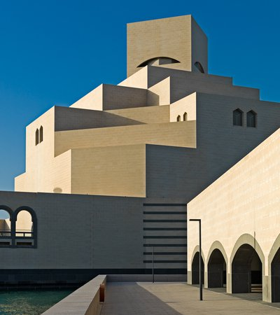 Detail view of the Museum of Islamic Art showing its angular architecture against a bright blue sky