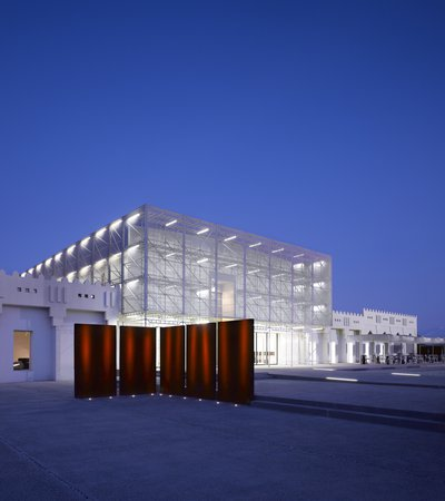 Exterior view at nighttime showing Mathaf's contemporary building brightly lit