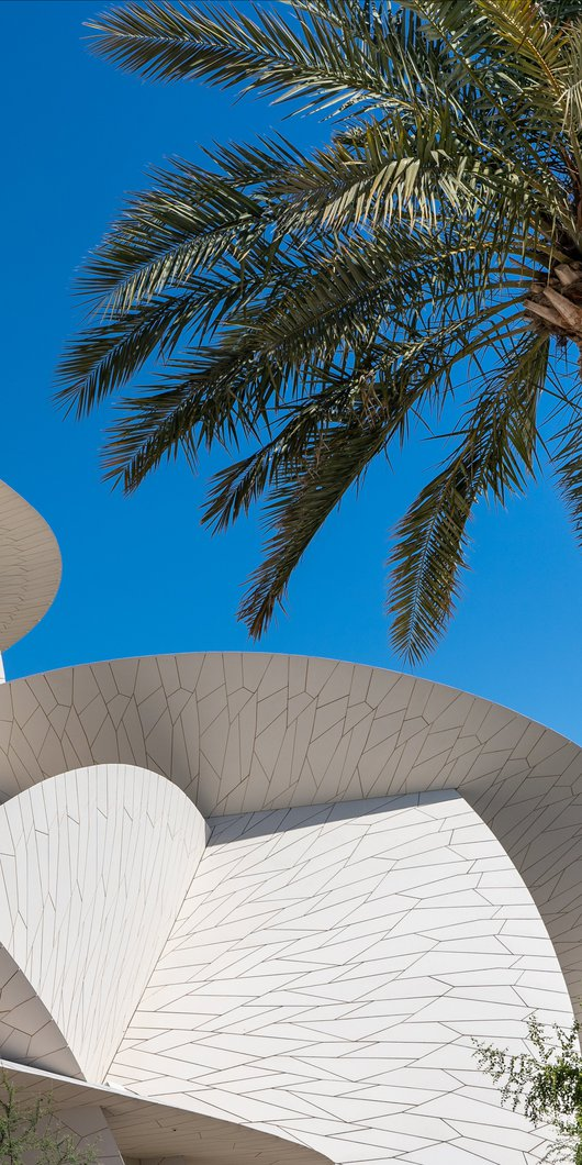 Decorated stone arches with a doorway in shade and a view of the National Museum of Qatar in the background