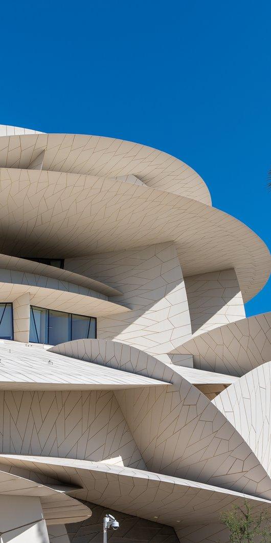 صورة تُظهر التصميم الخارجي لمتحف قطر الوطني على شكل أقراص في مقابل سماء الدوحة الزرقاء