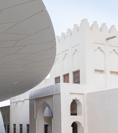 Exterior view showing the faceted shapes of the National Museum of Qatar on the left with the historic palace on the right
