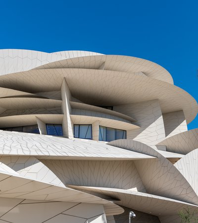 Exterior view of the National Museum of Qatar showing its angular disc like shapes against a blue sky