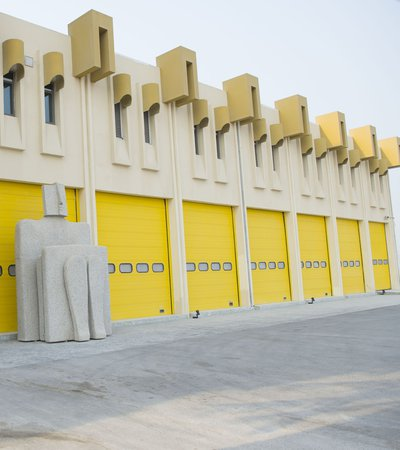 Exterior of The Fire Station Artist in Residence building showing its bright yellow shutter doors and sculpture at the entrance