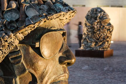 A focus on the sculptures wearing a soldier's helmet and the other wearing a face cover