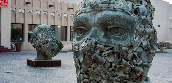 A close shot of two of the three sculptures showing heads wearing military gear, with one wearing a face cover and the other a gas mask
